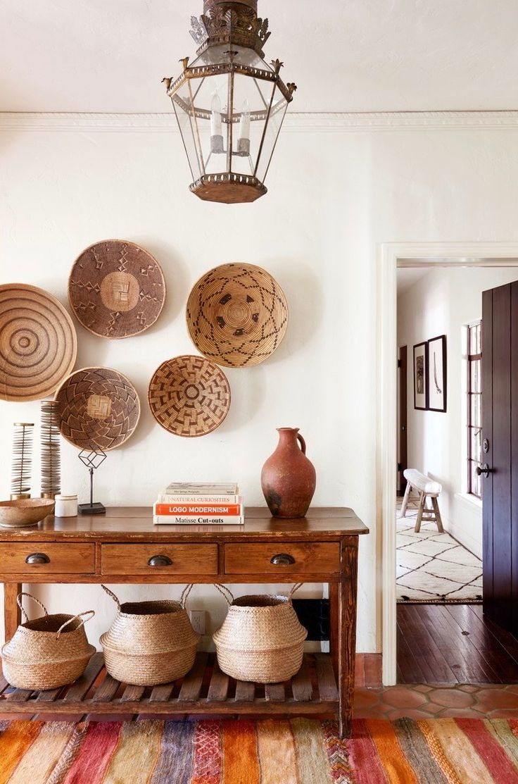 Get the Look! Interior Design Ideas from HOME AGAIN.Entryway or foyer with African baskets hung on wall, console table, and belly baskets. This is the Spanish hacienda house feature in HOME AGAIN movie starring Reese Witherspoon. #homeagain #entryway #foyer #interiordesign #africanbaskets