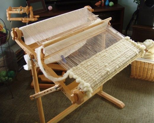 This is a Kromski Harp loom which has been set up with a cotton warp and a wool roving weft.   Also on this site, she shows how to weave with yarn on a potholder loom, etc.