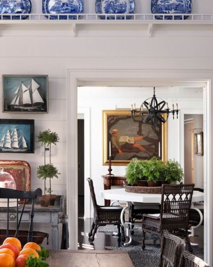 Don't you love all the wonderful details in this Nantucket home designed by @susanzisesgreeninc ? The blue and white plates on the wall, the nautical art, the plants, the wicker chairs, the orb light fixture...everything appeals to me!