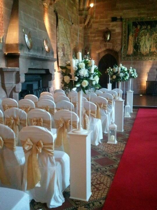 Peckforton castle wedding with gold taffeta sashes and cream candelabras with plinths