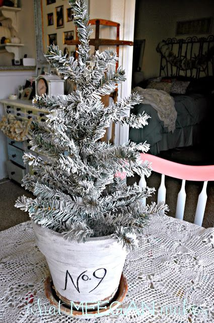 Under $3 DIY Flocked Christmas Tree.  dollar tree christmas tree, can of fake snow, and a antiqued and stenciled clay pot!  set some pine cones and oh la!