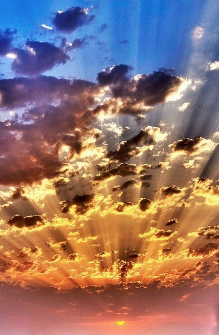 The sun rays piercing through the soft feathery clouds