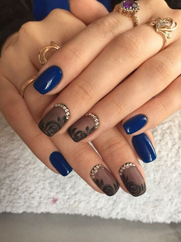 A really elegant looking blue rose nail art design. The roses are drawn in black ink and re on top of a black sheer nail polish to give out that silhouette look. The rest of the nails are painted in midnight blue polish with silver embellishments on the cuticles for more effect.