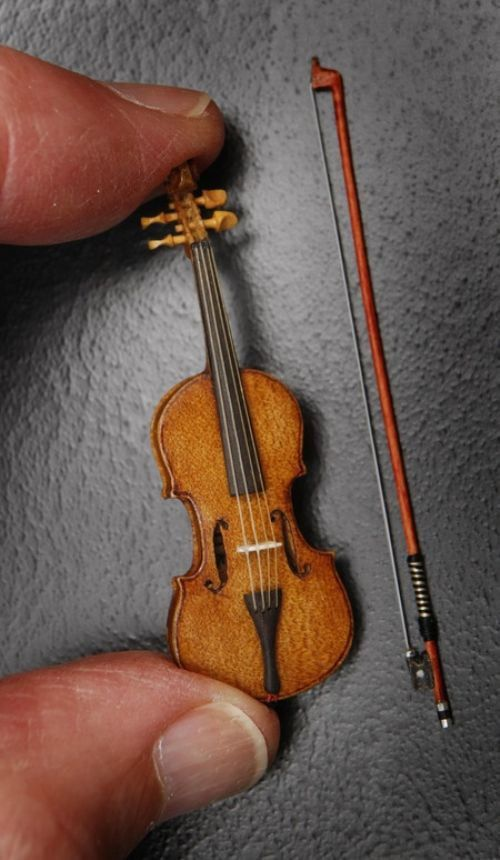 Wow! . . .Incredible miniature violin with bow.(Love the detail on the pegs and frog of the bow.  Wonder if it can actually be played)