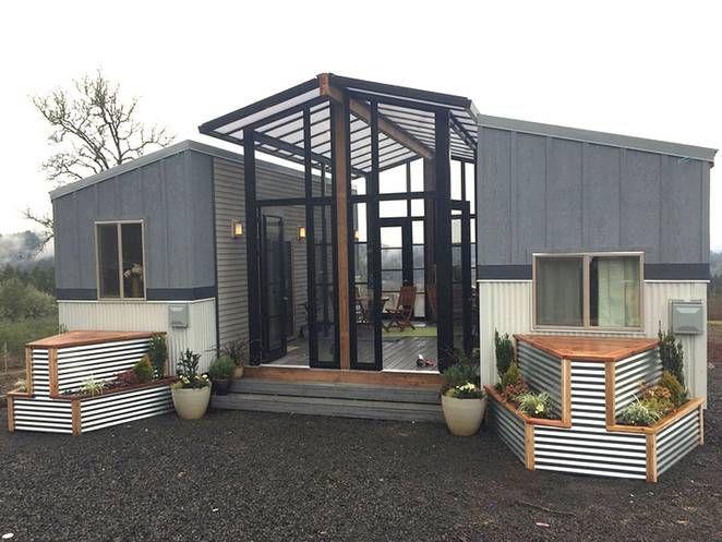 Zwei kleine Häuser mit einem zentralen Sonnenraum und Deck verbunden