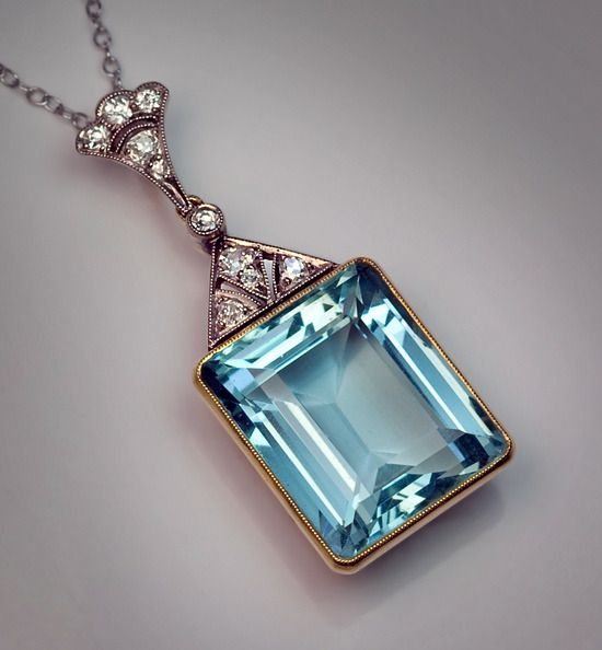Art Deco Russian Aquamarine Pendant c1930 emerald cut aquamarine (18 x 14 x 8.8 mm - approximately 15.19 ct) in a yellow 14K gold milgrain setting crowned by a triangular art deco style diamond-set mount and a plume shaped diamond bail.