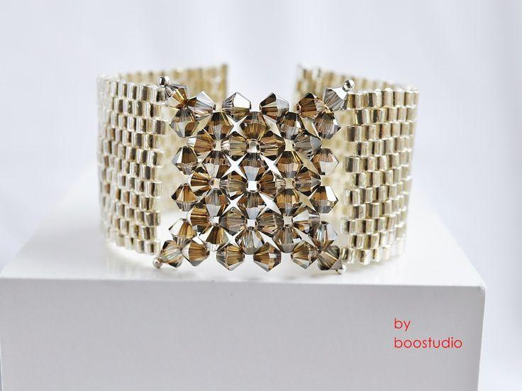 Bransoleta, wypleciona z najwyższej jakości drobnych, japońskich koralików Miyuki Delica i kryształków Swarovskiego Bicone w kolorze Crystal Bronze Shade. Szerokość 3 cm. , długość 17,5 cm z wygodnym posrebrzanym zapięciem zatrzaskowym. https://www.facebook.com/BooStudioHandMade