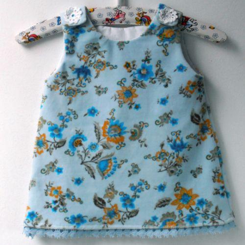 babyjurkje Kitty van zachte rekbare veloursstof. Onderaan een gehaakt randje en op de schoudertjes (hand) gehaakte bloemetjes. Love it.