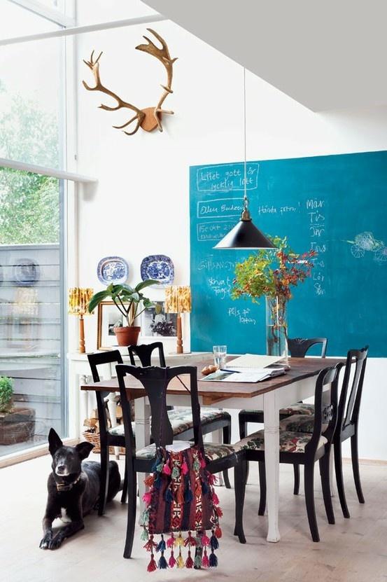 Felgekleurd schoolbord boven de eettafel.  En gewei