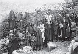 Chrétiens de la tribu des 'Azeizât à Madaba (Jordanie), comme l'atteste la présence d'une petite croix portée par le bébé, à gauche de la photographie. Le cliché est pris probablement à l'occasion d'un baptême. 1905