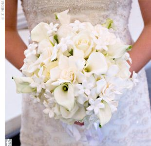 Emily's textured, all-white bouquet was made up of calla lilies, roses, stephanotis, and gardenias. Emily also had her late grandmother's cross wrapped around the stems in her honor.