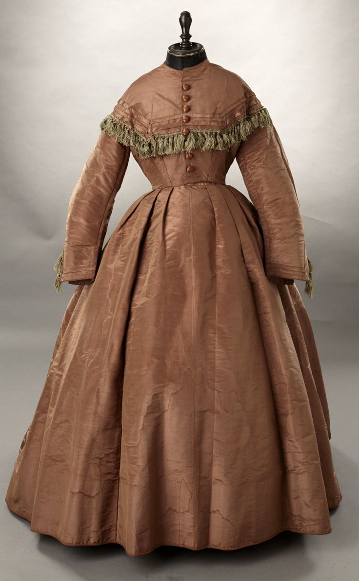 1860s Cocoa brown moire silk dress with light green silk fringe. The dress closes down the center front with hooks. The dress has the sloped, drop shoulders of the period. Lined in glazed brown cotton