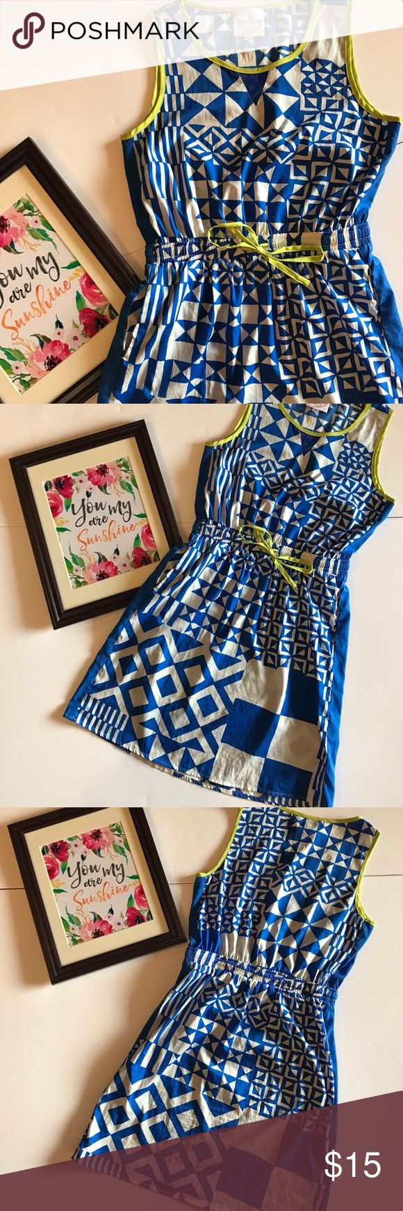 Romeo & Juliet Couture dress Geometric print blue and white sleeveless dress w/ neon yellow around scoop neck, arms and tie at elastic waist. Also has a sheer blue material in shape of a V at the bottom of the scoop. Pull over style. 100% polyester. In good condition. Romeo & Juliet Couture Dresses