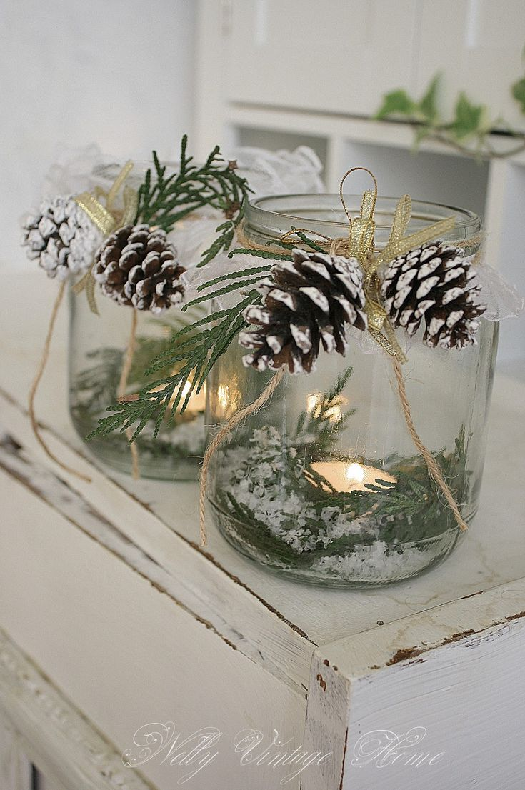Vintage table decorated with tea lights & pine in simple glass jars.