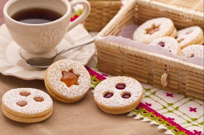 I biscotti tirolesi con confettura di fragole sono di pasta frolla farcita con confettura di fragole e spolverizzati con abbondante zucchero a velo.