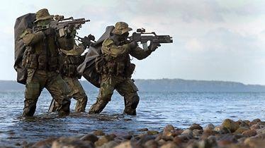 Kampfschwimmer nähern sich aus dem Wasser und sichern den Strandbereich.