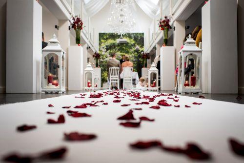 Ook de ceremonie wordt basic wit met rode elementen. Als de bruidsmeisjes komen en vooral het kleine jongetje en meisje die dan rode rozenblaadjes strooien op de 'loper'.