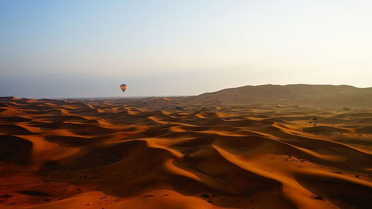 """""""About 30 minutes after sunrise a hot air balloon is captured in the distance beginning it's decent to land in a camel farm. The image was shot while floating over the dunes in a chase balloon."""" Photo by Gareth Lowndes, New Zealand"""