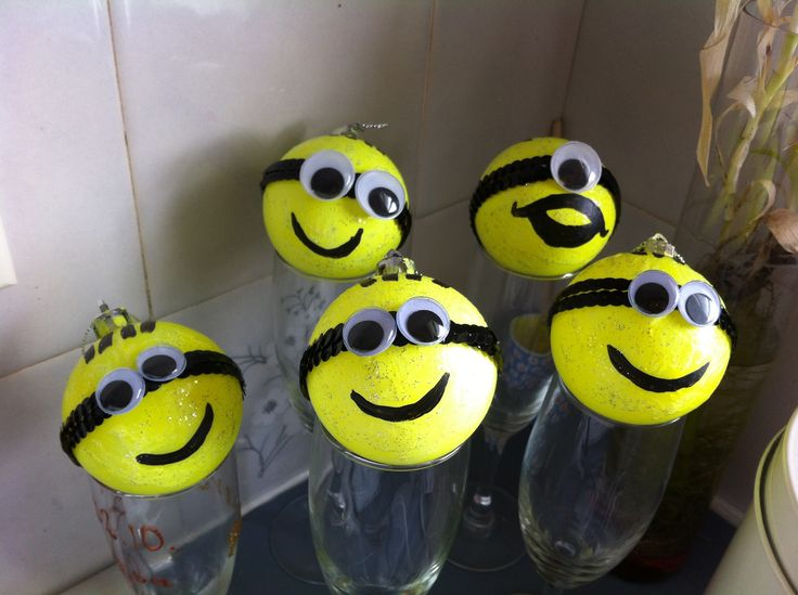 Minion Xmas Baubles Painted with fluorescent  yellow acrylic paint, glitter,  craft sticky eyes and black acrylic paint for the mouth and hair Not Branded.
