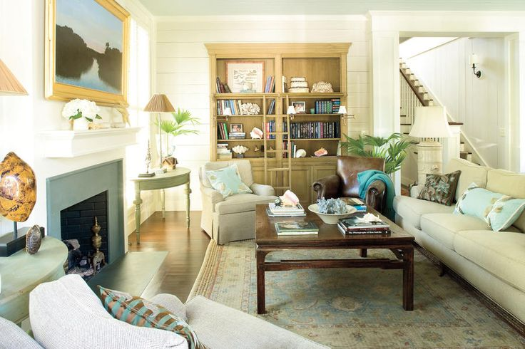Tortoise and conch shells accessorize this coastal living room, while starfish adorn the mantel. Books on South Carolina's coastal area lie stacked on the coffee table and topped with shells. Vases of palm fronds simply picked up from outside complete the tropical decor.  See this Coastal-Style Cottage