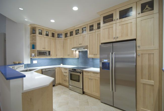 This kitchen is so simple and pretty. The light cabinets, floors and counters keep it very clean looking, and the blue backsplash tile adds some lovely color.