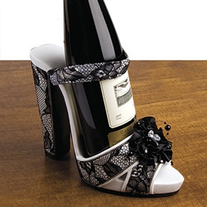 "High Heel Wine Holder   $34.98    Product # SM960 - Dress up your favourite bottle of wine with a stylish high heel shoe! With strappy design, jewelled floral bow and ultra-high lace-covered heel, this wine holder shoe is the perfect gift for wine lovers. Holds a standard 750mL bottle.sorry, wine bottle not included. Made of polyresin. 8-1/2""L x 6""H x 4""W"