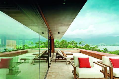A varanda da piscina é larga e confortável. Repare que os andares acima são recuados para não tirar a sensação de amplidão de quem relaxa nas chaises da Casual. Almofadas desenhadas pelo escritório Bernardes Arquitetura.