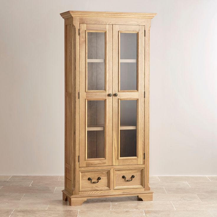 The elegant Edinburgh Natural Solid Oak Display Cabinet has two glass doors  that protect the display shelves. The base