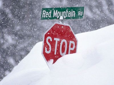 Stop sign buried in snow, Red Mountain Road. Red Mountain is a small mining town in British Columbia