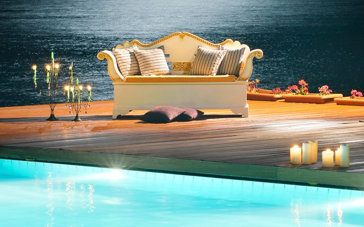 Luxury, designer sofa with striped pillows under the moonlight, by the pool and the sea with candlelight. Visit www.kassandrabay.com/hotel-pools for more info.