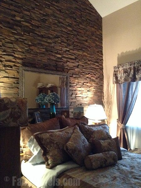 faux stone panels create a rugged accent wall for a bedroom