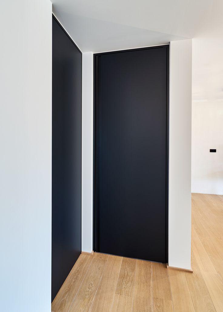 Zwarte binnendeur van vloer tot plafond voorzien van een speciale Traceless Soft coating. Deze afwerking is vingerafdruk werend en makkelijk te reinigen. De verticaal ingebouwde handgreep over de ganse deurhoogte is van zwart geanodiseerd aluminium gemaakt. #zwartedeur #zwartebinnendeur