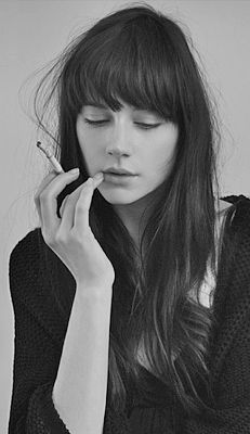 Long brown hair with long lash-length fringe, tapered to nearly cheekbone length and worn with a slight curl or bend. Cut from a very full triangular section at the crown of the head.