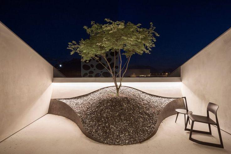 """An outdoor space described as a """"zen garden"""" incorporates a curvaceous planter containing a jasmine tree."""