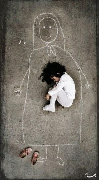 A child in the orphanage in India is missing her mother. She drew her mother on the ground and lay.