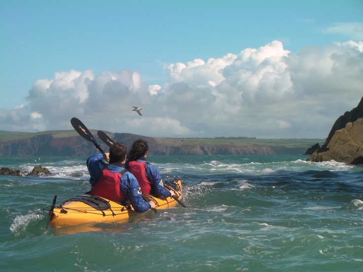 A double sea kayak paddling the  Pembrokeshire Coast from Fishguard to Newport on a guided seakayaking trip with Mayberry Kayaking