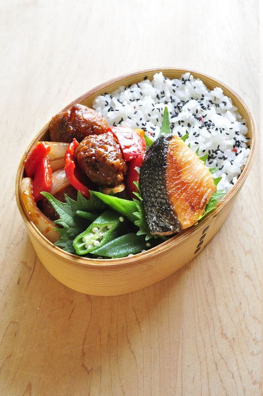 Grilled Salmon Bento Box, featuring sides of Italian chicken salad, okra, meatballs, and rice topped with black sesame seeds