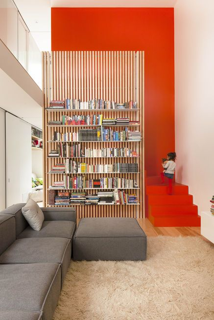 La SHED Architecture // Maison de Gaspé in Montreal ; The stairs are partically hidden behind a slatted ash screen that supports steel bookshelves. painted bright orange Photo by: Maxime Brouillet