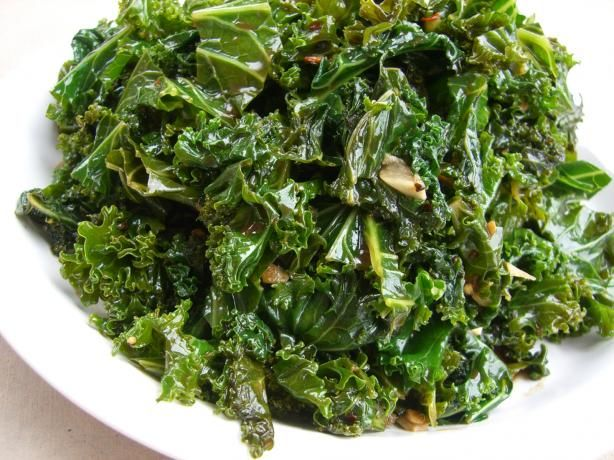 1 1/2 lbs kale, stems and leaves coarsely chopped     2 tablespoons olive oil     crushed red pepper flakes, to taste (optional)     2 garlic cloves, finely sliced     1/2 cup vegetable stock or 1/2 cup water     salt and pepper     2 tablespoons balsamic vinegar