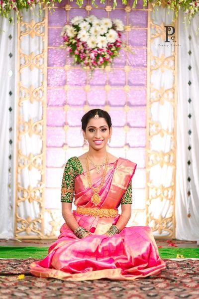 pink kanjivaram saree, elbow length sleeves, green blouse, contrast blouse with kanjivaram sarees, layered jewellery, bride sitting on floor, telugu bride, pink and green kanjivaram saree, pattu sarees