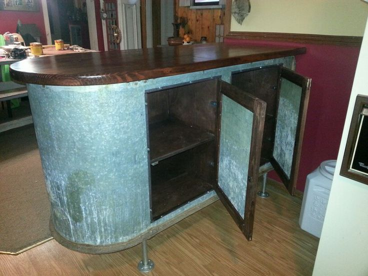Industrial rustic kitchen Island made from galvanized water trough.  New custom built cabinets were installed to create useful storage
