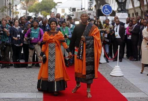 Mandla Mandela, right, the grandson of former South African President Nelson Mandela arrives on the red carpet, with his wife, left, at Parliament, as they await South African President Jacob Zuma's, State off the Nation address in the city of Cape Town, South Africa, Tuesday, June 17, 2014. (AP Photo/Schalk van Zuydam)