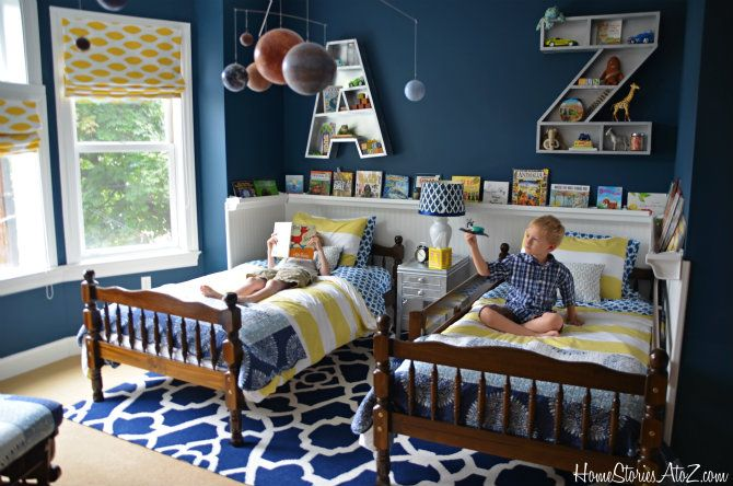 I love so much about this room. I'm crazy about the monogram bookshelf on the walls and the raingutter bookshelf chair rail! I love the colors. The strong blues and yellows on the walls, rug, and bedding, with the silver accents in the letter bookshelves and nightstand. Super cute and fun.