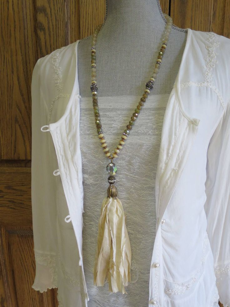 This Off White sari silk tassel necklace is a beautiful neutral necklace. Ive hand knotted semi precious beads with Czech Picasso glass rondelles with a sturdy nylon cord. Czech glass crystal, rhinestones round beads, rhinestones rondelles and gold hematite beads add a sparkling touch