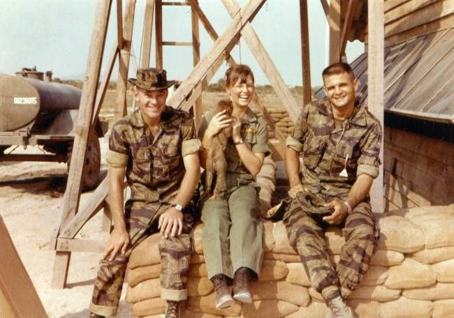 Three American personnel pose for a photo with a puppy at their base in Vietnam