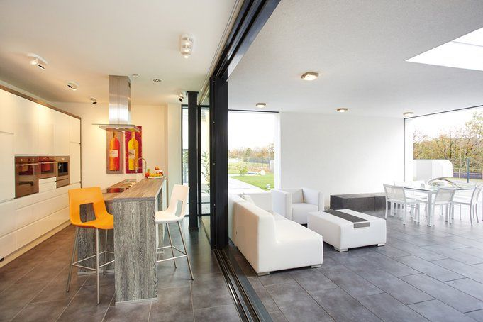 Die riesigen Fensterflächen lassen sich mit nur einem Finger öffnen. So verschmelzen Küchen- und Außenbereich miteinander zu einem Raum.