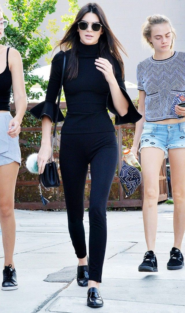 Kendall Jenner wears a high-neck top with ruffle sleeves, aviator sunglasses, skinny jeans, loafers, and a mini bucket bag