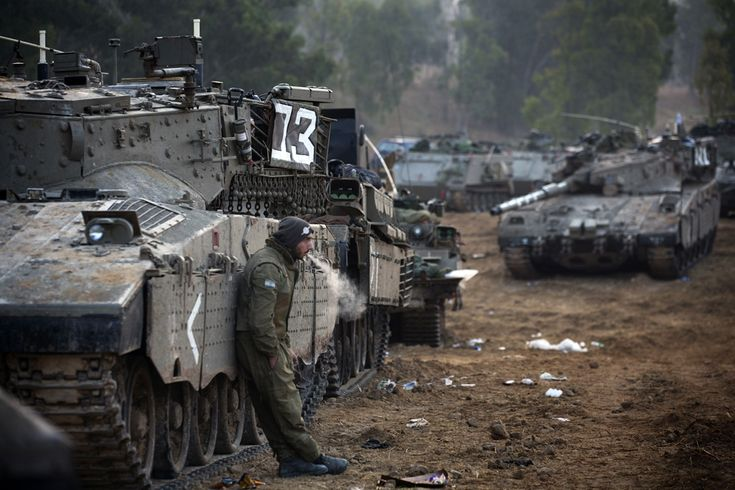 An Israeli soldier smokes a cigarette next to a convoy of tanks at an Israeli army deployment area near the Israel-Gaza Strip border as they prepare for a potential ground operation in the Palestinian coastal enclave, November 19, 2012.