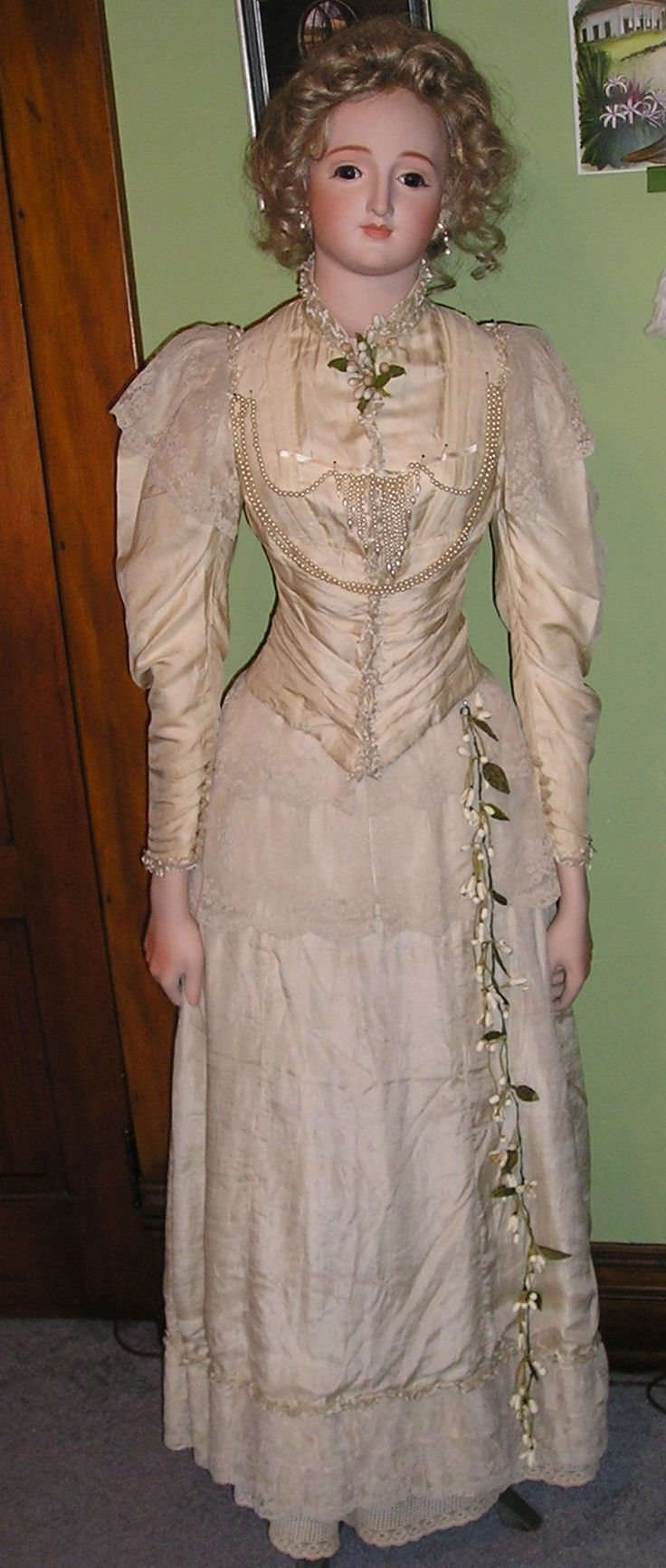 "I believe that this gown is two ""married"" pieces, in that they are not original to each other.  The top is a very fine ivory wool and the skirt may actually have been an underskirt.  The ensemble had been used in vintage fashion shows before it came to me.  I added the antique ruching, lace and orange blossoms."