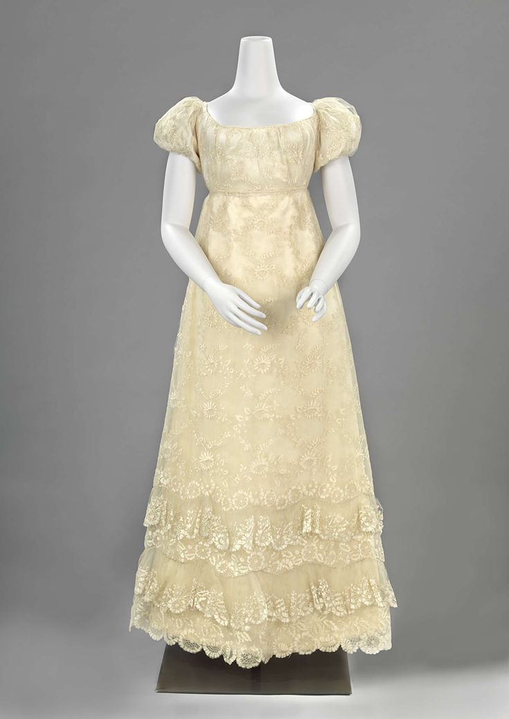 Gown: ca. 1815-1820,  silk lace with low cut neckline and puffed sleeves, lace with a pattern of wreaths, flowers and leaves.